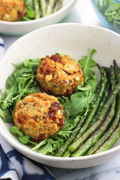 Sun-dried tomato and pesto tuna cakes are a flavorful, healthy meal that comes together in just about 30 minutes - a great weeknight dinner recipe! These tuna cakes are baked and served over a bed of arugula and alongside easy pan-roasted asparagus.