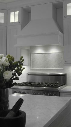 Beacon St. Kitchen - Carrara marble countertops and accent medallion behind the stovetop, Waterworks white thassos mini-brick backsplash tiles, Wolf appliances..