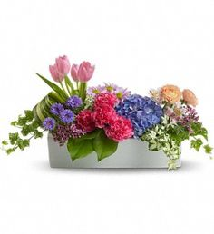 Garden Party - blue hydrangea, light pink tulips and alstroemeria, hot pink carnations, orange, ranunculus, purple matsumoto asters, lavender daisy spray chrysanthemums and waxflower plus fresh spring greens
