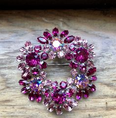 Sherman wreath brooch set with fuchsia, light rose and light rose AB Swarovski , rhodium plated.