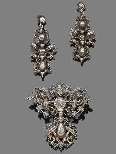 A mid 18th century diamond brooch and pendent earring suite  The brooch of openwork design, composed of a series of interlaced scrolls and ribbons highlighted with rose-cut diamonds, suspending an articulated drop, mounted in silver closed-back settings with yellow gold accents, accompanied by a pair of pendent earrings of similar design, brooch and earrings with later fittings, lengths: brooch 4.5cm, earring 4.0cm