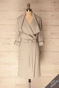 Elemir Grey Knee-Length Wrap Trench Coat | Boutique 1861  This trench coat from Montreal based brand SOIA & KYO is versatile and elegant. The draped collar can be worn multiple ways and the rolled-up sleeves add a casual chic touch. The straight silhouette falls to the knees.  #springjacket