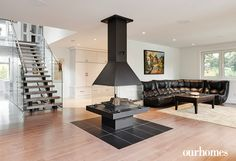 """A central gas fireplace in the open-concept main living area is a focal point. Having the fireplace in the centre keeps the exterior walls free for windows.   See more of this home in """"Bright Home on Secret Ottawa Lake Goes Modern"""" from OUR HOMES Ottawa Summer 2016 http://www.ourhomes.ca/articles/build/article/bright-home-on-secret-ottawa-lake-goes-modern"""
