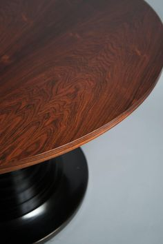 Round polished wood top over a black-lacquer, stepped trumpet column on a round base with a patinated brass band.Literature: Domus No. 410, December 1964; Rivista Dell'Arredamento, December 1963, page 33.