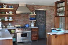 Warm wood cabinetry, exposed red brick, open shelving, stainless steel appliances, light colored counters and bright robins egg blue accents