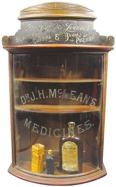 Dr. J. H. Mc Lean's Curved Glass Store Display Case and 2 product bottles. Etched glass front with 3 wood shelves. Very good original condition. 17 1/2 X 27 1/2 X 7 1/2 inches. - by Showtime Auction Services