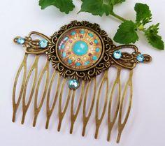 Nostalgischer Haarkamm aus antikgoldfarbenem Metall mit einer filigranen Fassung und einem handgearbeiteten Glas Cabochon mit Juwelen-Motiv. Der Ka...