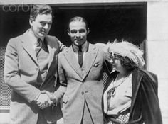 Original caption: Rudolph Valentino, screen star, whose marriage to Winifred Hudnut resulted in his being arrested for bigamy, was released on bail furnished by June Mathis, scenario writer, at the right, and Thomas Meighan, screen star at the left. Valentino had secured an interlocutory decree of divorce which did not permit him to remarry for at least a year.