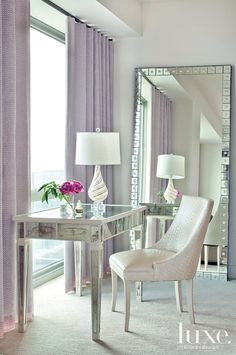 Homeowner Kristin Lee says the magenta Barbara Barry chair in the master bedroom is one of her favorite pieces in the condo she shares with her family during baseball season. Against views of Philadelphia, a Lee Industries sofa paired with Barbara Barry's Arclight silver-leaf cocktail table offer a retreat for the lady of the house.