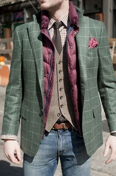 Rock a purple quilted gilet with blue jeans to get a laid-back yet stylish look.  Shop this look for $146:  http://lookastic.com/men/looks/tie-longsleeve-shirt-pocket-square-gilet-waistcoat-belt-blazer-jeans/4689  — Dark Brown Tie  — Brown Chevron Longsleeve Shirt  — Purple Pocket Square  — Purple Quilted Gilet  — Brown Wool Waistcoat  — Brown Leather Belt  — Dark Green Plaid Blazer  — Blue Jeans