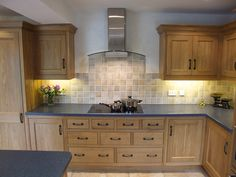 Traditional Oak kitchen happily wears black wrought iron door furniture, with blue corian worktops, plus stainless steel appliances.
