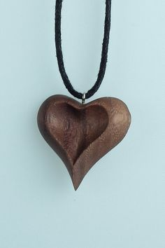 One sided heart pendant hand carved from beautiful American black walnut. - Walnut, sanded to a smooth finish - Non-toxic oil finish to seal the wood & enhance its natural color - Pendant size: 32 mm - On adjustable black cotton cord necklace Wood Carving Designs, Wood Carving Art, Wooden Necklace, Wooden Jewelry, Simple Wood Carving, Celtic Necklace, Wooden Hearts, Heart Jewelry, Creations