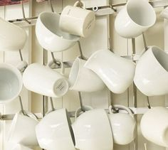 Assorted white mugs and mug organizer