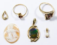 Lot 220: Mixed Gold Jewelry Assortment; Including 10k gold rings both having garnets and 14k gold pendants, most marked; together with carved shell cameo
