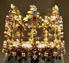 Front of the crown of Princess Blanche. c 1370-80. It is of gold set with sapphires, rubies, pearls and diamonds and eight 14th century imitation diamonds. Enamelled decoration is applied to the circlet. This is a typical example of the longer fleurons seen from the late 14th century on.