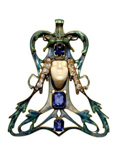 René Lalique. Woman Face Pendant c. 1900 - 1902. Pendant trapezoidal shape, with the center a female face carved in ivory and topped by the head of a chimera in enamelled gold, snapping a sapphire with cutting scissors. In the framing of algae in enamelled gold blue, set up under the face, another two sapphires with cutting scissors. On the figure, two rods suggest hair, studded with old-cut diamonds and rose-cut. Wire small bars of square section in enamelled gold green.