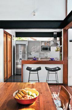 Um balcão de alvenaria com tampo de ipê divide sala e cozinha. No alto da parede, o vidro fixo instalado abaixo da viga metálica permite a entrada de luz.