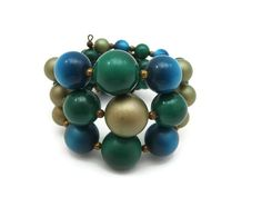 A beautiful vintage moonglow lucite wired bracelet, in gold, teal and green. Its open at the back making it adjustable. The gold tone beads have a