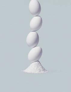 Four eggs stacked on a pile of powder © Virginie Gosselin / Offset