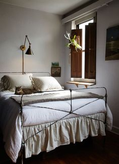 Beautiful, moody bedroom featuring a thin iron bed frame, wooden shutters, ruffle bedding and low lighting