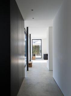 Nowoczesny korytarz, betonowa podłoga, czarna garderoba. Zobacz więcej na: https://www.homify.pl/katalogi-inspiracji/39901/ferrari-wsrod-domow-jednorodzinnych