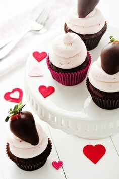 Simple chocolate cupcakes are topped with strawberry infused buttercream and finished with a chocolate covered strawberry.