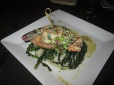Pan Seared Salmon on a bed of garlic mashed potatoes, broccoli rabe, and topped with a giant shrimp with garlic butter sauce and micro greens.