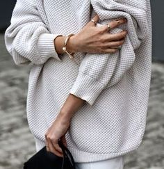 Grey textured sweater. Black clutch. Golden jewelry. Style.