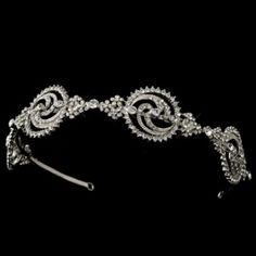 "Simple yet stunning, this modern headband dazzles with a unique design accented with sparkling clear rhinestones. A single hoop is stationed at the end of this hand band to secure the headpiece in place. Perfect accessory for your wedding, prom or anytime you just want to add sparkle to your hair on a special night out.  Band - 14 1/2""x Design - 11"" x 1 1/4"""