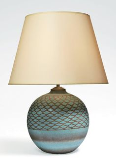 Jean BESNARD (1889-1958) Lampe boule à décor de croisillons Lampe boule émaillée bleu craquelé, partiellement essuyé sur la partie basse de la panse.La partie supérieure est quant à elle habillée d'un décor de croisillons obtenus par enlevage de l'émail,et formant une résille de losanges bleus.La lampe est surmontée d'un abat-jour de couleur crème refait dans l'esprit du modèle original.Circa 1930 Hauteur totale: 53 cm Diamètre de l'abat-jour:40 cm Hauteur du pied:26,5 cm Diamètre du pied:25…