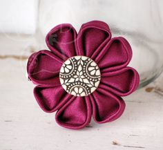 Vintage Merlot satiny daisy style kanzashi flower is perfect for a reserved look.    The daisy wine hued flower is finished with a vintage decorative button center and secured to an alligator clip for wear in your hair, clipped to your lapel, headband, purse or more.  Our art and accessories ...