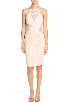 Delicate floral lace insets add a feminine touch to this nude colored sheath dress with a shoulder-baring high neck.