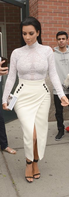 Kim Kardashian signed copies of her book, Selfish, wearing a white mesh embroidered turtleneck, asymmetrical midi skirt, and black ankle strap sandals, making us wonder if this is the street style version of her Roberto Cavalli sheer gown from the Met Gala.