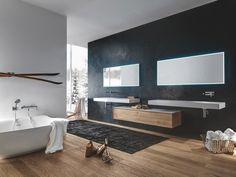<p>Cette salle de bain associe un meuble de rangement suspendu en chêne massif habillé d'une plaque en cristalplant faisant écho aux deux plans vasque suspendus de même mati...