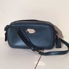 "NWTCOACH Pebbled Leather Crossbody Pouch Charmingly proportioned in soft ""Metallic Blue"" pebble leather with a buttery soft hand feel and a subtle sheen, this lightweight, shaped piece has just enough space for phones, cards, keys and other sundries...plus pockets to keep them in place. Zip top closure. 50"" Adjustable strap for shoulder or crossbody wear. Perfect piece to throw this into a tote taking you from day to night! Coach Bags Crossbody Bags"