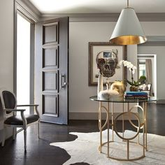 A black paneled front door opens to a contemporary foyer features a Goodman Hanging Lamp illuminating a round glass top foyer table with a gold leaf base atop a white cowhide rug.