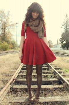 Red dress with sleeves, tights, and lace up boots.