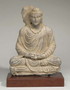 a gandhara grey schist figure of buddha sakyamuni   3rd century   Seated in vajrasana on a throne, both hands in dhyanamudra, wearing pleated cloak, his face with serene expression, arched eyebrows above downcast eyes, elongated earlobes, wavy hairdress combed in an usnisha and head halo behind  32.6 cm high, mounted