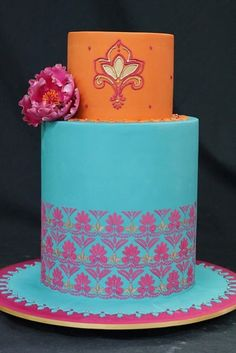 A cake of turquoise blue and tangerine orange, highlighted with fuchsia pink. Almost too pretty to eat.