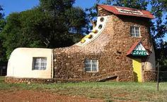 Shoe house (Mpumalanga/ South Africa) The 'shoe house' is the work of artist and hotelier Ron Van Zyl, who built it for his wife Yvonne in 1990. The shoe houses a little museum of sorts, showcasing Van Zyl's wood carvings. The shoe is part of a complex that includes an eight-chalet guest house, camp site, restaurant, pool and bar.