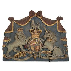 Carved wood Coat of Arms.  England  1810  A good quality carved wood, painted and gilded Royal Coat of Arms with the lion and unicorn beneath a gathered draped panel.    Ex collection of the late Melvin Belli.  (the harp representing Ireland)