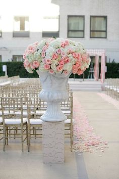 White washed urn filled with pink roses and white hydrangeas—flanked a ceremony aisle.