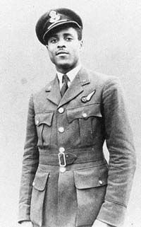"Flight Officer Johnny Smythe, from Sierra Leone, enlisted in the RAF in 1939.  He was one of four out of a class of 90, to complete the tough training to be a Navigator. On his 28th bomber mission, in November 1943, he was wounded, shot down, and captured by Germans who could not believe they were looking at a Black officer. In Stalag Luft One, Smythe worked on the escape committee, but couldn't break out himself: ""I don't think a six-foot-five black man would've got very far in Pomerania."""