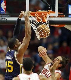 Utah Jazz forward Derrick Favors (15) dunks the ball in front of Chicago Bulls center Joakim Noah during the first quarter of an NBA basketball game in Chicago, Friday, Nov. 8, 2013. (AP Photo/Kamil Krzaczynski)