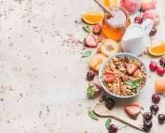 #Healthy breakfast ingredients  Healthy breakfast ingredients. Oat granola in bowl with nuts strawberry and mint leaves milk in pitcher honey in glass jar fresh fruits and berries on light concrete background top view selective focus copy space horizontal composition