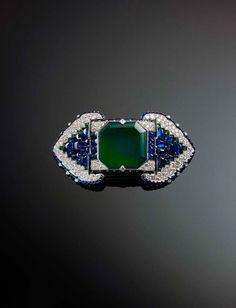 Belt Brooch by Cartier, circa 1920-30. Platinum, set with emeralds, sapphires and diamonds