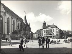 Gezicht op de Grote Markt gezien vanuit het noord-oosten, 1979. Zicht op de Grote of St. Michaels Kerk en de Harmonie, op het begin van de Luttekestraat en de Melkmarkt. Te zien zijn de winkel van Van Beek aan de Grote Markt en de ABN Bank en het pand van de Zwolsche Courant aan de Melkmarkt. Op de voorgrond wanderlende mensen en mensen die op banken op de Grote Markt zittten.De Peperbus staat in de steigers i.v.m. renovatiewerkzaamheden.