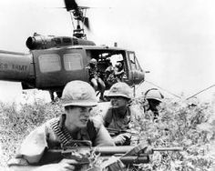 American soldiers exit a helicopter during Operation Oregon in the Vietnam War…