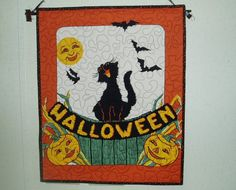 This Halloween Wall Hanging is quilted with 100 % Cotton Fabric. It measures 17 1/2 x 21 1/2. It has a layer of cotton batting and is machine quilted. The back is black with tiny orange moons and stars. There is, also, a special sewn area on back to insert dowel for hanging