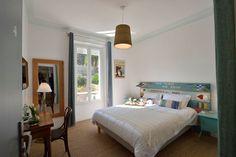Une jolie chambre à la déco chaleureuse agrémentée d'une tête de lit en planches de bois peintes